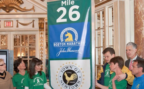 The mile marker that will hang at the end of the 26th mile will feature the city seal surrounded by 26 stars, one for each victim.